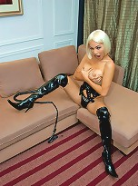 Leather clad blonde shemale mistress holds a whip