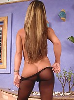Kinky shemale in spike heel shoes playing with her pantyhosed cock on floor