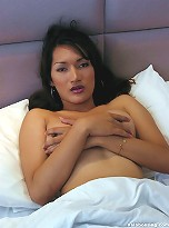 Thai ladyboy jerks off own dick in bed