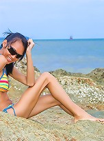 Leggy tranny posing in stripy bikini on the beach